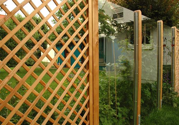 Holzzaun mit Glasscheiben als Lärm und Windschutz in München